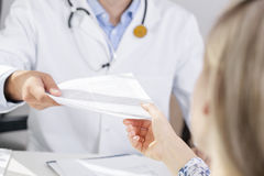 Doctor give a document to patient Stock Photography