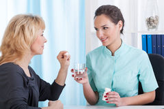 Doctor gives drugs and water to the patient Stock Photos