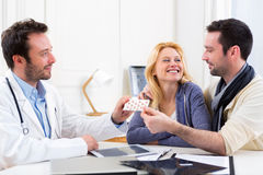 Doctor gives pills to couple of patient Stock Image