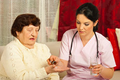 Doctor gives pills to senior woman Stock Photo