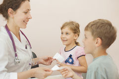 Doctor gives recipe for girl and boy Royalty Free Stock Photos