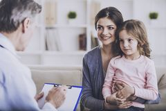 Doctor Gives Recommendations. Smiling Little Girl And Mom.. Doctor Calms of Small Patient. Family on Consulation of Pediatrician. Healthcare Concept. Happy stock photos