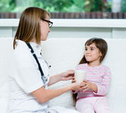 Doctor gives to drink to the sick child Stock Photos