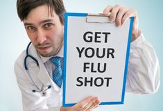 Doctor is giving advice to get your flu shot. View from top stock images