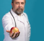 Doctor giving apple for healthy eating Royalty Free Stock Photography