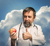 Doctor giving apple for healthy eating Stock Photography