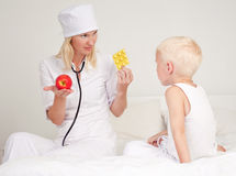 Doctor giving apple and pills Stock Photos