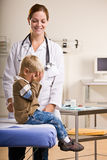 Doctor giving boy checkup in doctor office Stock Photo