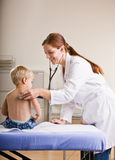 Doctor giving boy checkup in doctor office Royalty Free Stock Photos