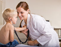 Doctor giving boy checkup in doctor office Stock Images