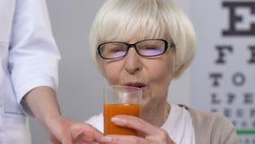 Doctor giving carrot juice to elderly female patient in eyeglasses, vitamins. Stock footage stock video