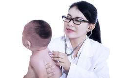 Doctor giving checkup with stethoscope to baby Stock Image