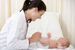 Doctor giving checkup to baby in exam room Stock Image