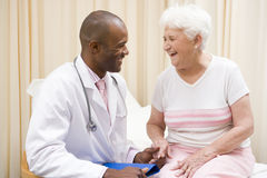 Doctor giving checkup to woman in exam room stock images