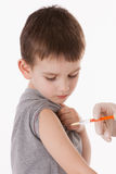 Doctor giving a child injection in arm. On  image Stock Photography