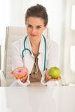 Doctor giving a choice between apple and donut Stock Images