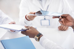 Doctor giving clipboard to his colleagues Royalty Free Stock Image