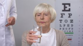 Doctor giving elderly female patient pill, reducing high eye pressure, vitamins stock footage