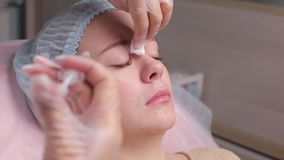 Doctor giving face lifting injection on mid age woman in the forehead between eyebrows to remove expression wrinkles in. A clinic surgery room O.R background stock video footage