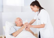Doctor giving glass of water to senior man Royalty Free Stock Photos