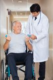 Doctor Giving Hand Weights To The Senior Man Royalty Free Stock Photos