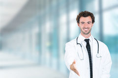 Doctor giving handshake smiling standing in hospital hallway Royalty Free Stock Photo