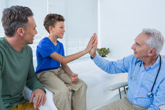 Doctor giving high five to a patient Royalty Free Stock Images