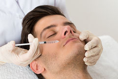 Doctor Giving Injection On Face Of Man Royalty Free Stock Photos