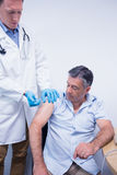 Doctor giving injection to his patient Stock Photos