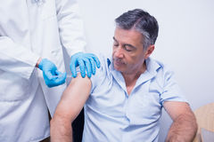 Doctor giving injection to his patient Royalty Free Stock Photography