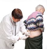 Doctor giving injection to old woman. Doctor giving injection to old women on a white background Royalty Free Stock Images