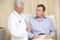 Doctor giving man checkup in exam room royalty free stock images