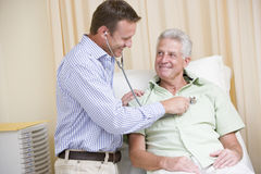 Doctor giving man checkup with stethoscope in exam Royalty Free Stock Image