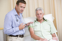 Doctor giving man needle in exam room Royalty Free Stock Photos