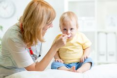Doctor giving medicament to kid with a spoon Stock Images