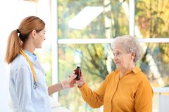 Doctor giving medication to elderly patient stock photos