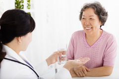 Doctor giving medication and water to senior woman Royalty Free Stock Image