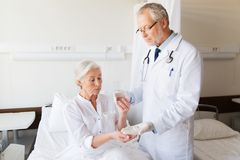 Doctor giving medicine to senior woman at hospital Royalty Free Stock Images