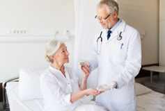 Doctor giving medicine to senior woman at hospital Royalty Free Stock Photography
