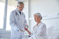 Doctor giving medicine to senior woman at hospital Stock Photography