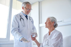 Doctor giving medicine to senior woman at hospital Stock Photos