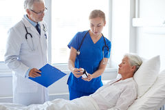 Doctor giving medicine to senior woman at hospital Royalty Free Stock Image