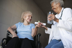 Doctor Giving Medicines To Disabled Patient stock photo