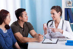 Doctor giving medicines to diverse couple Royalty Free Stock Photos
