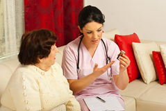 Doctor giving medicines to elderly woman. Doctor giving medicines and explaining how to take pills to elderly women at home Stock Image