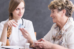 Doctor giving medicines to patient. Doctor giving medicines to senior woman, during home visit Stock Image