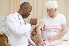 Doctor giving needle to woman Stock Images