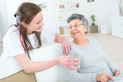 Doctor giving old lady glass water royalty free stock photos