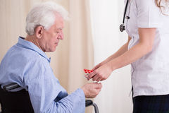 Doctor giving patient medicament. Close-up of doctor giving disabled patient medicament Stock Image