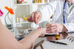 Doctor giving a pill to his patient Stock Photos